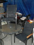 A circular garden table and 2 metal and mesh framed garden chair with teak arms.