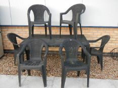 A green plastic garden table and 6 chairs.