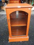 A teak effect music/hi-fi cabinet with bevelled glass door.
