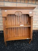A stained pine kitchen shelf unit.