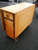 A good oak drop leaf table with end cupboard and drawer.