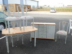 A painted pine sideboard with 2 doors and 4 central drawers together with pine table and 4 chairs.