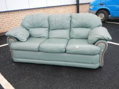 A green leather sofa in good condition.