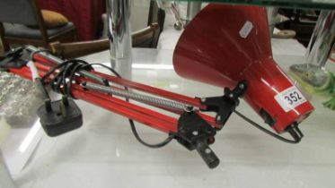 A red anglepoise lamp (missing base).