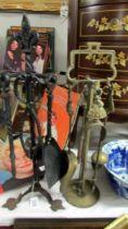 A brass companion set and a wrought iron companion set.