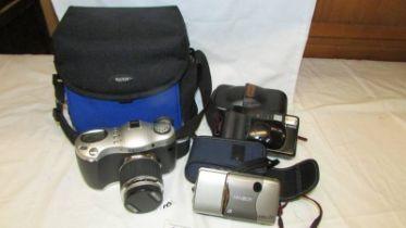 An HP Photosmart camera, a Canon Camera, A Minolta camera and a Kodak camera case.