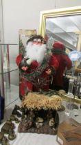 A Christmas tree, a Santa Clause figure and a Nativity scene.