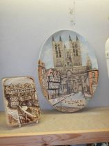 An oval wall plaque depicting Lincoln Cathedral signed Roy Fisk and another Lincoln wall plaque.