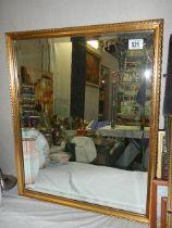 A gilt framed bevel edged mirror.