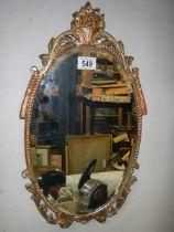 A gilt framed oval bevel edged mirror.