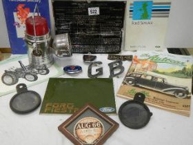 A mixed lot of motoring items including badges, tax disc, books etc.