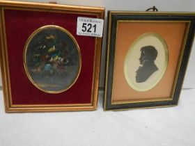 A framed and glazed silhouette and a floral painting.