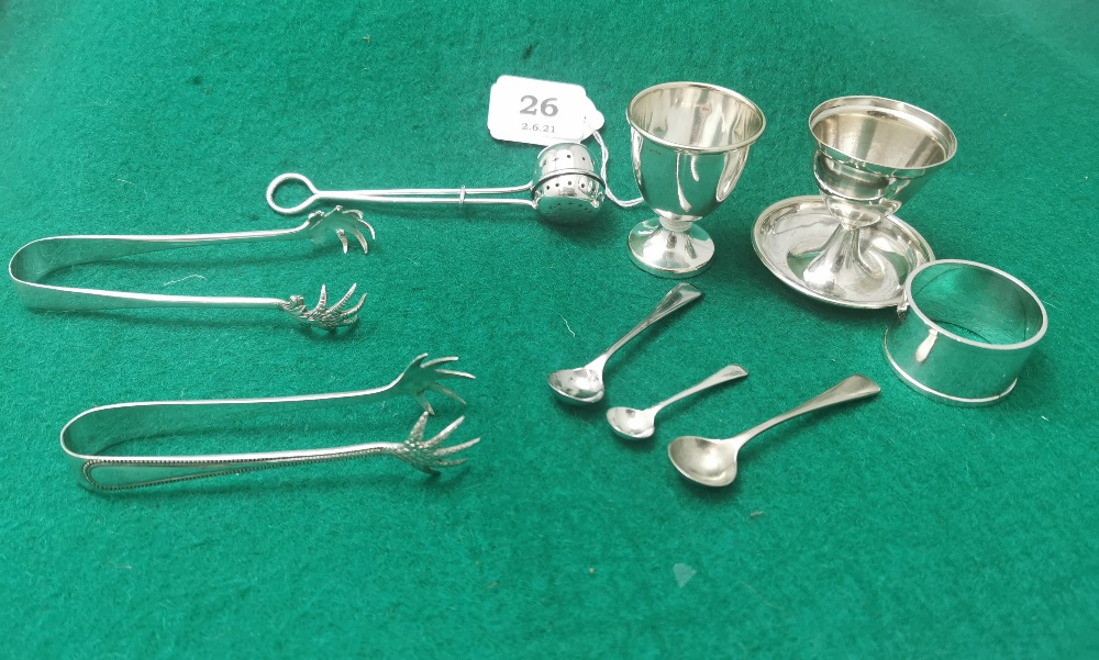 9 Pieces EPNS - two egg cups, a tea strainer, 3 salt spoons, 2 sugar tongs, 1 napkin ring (9)