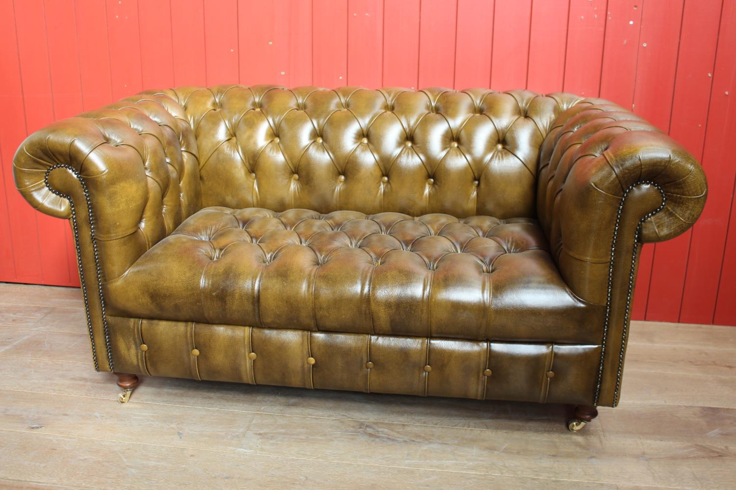 Deep buttoned leather upholstered settee.
