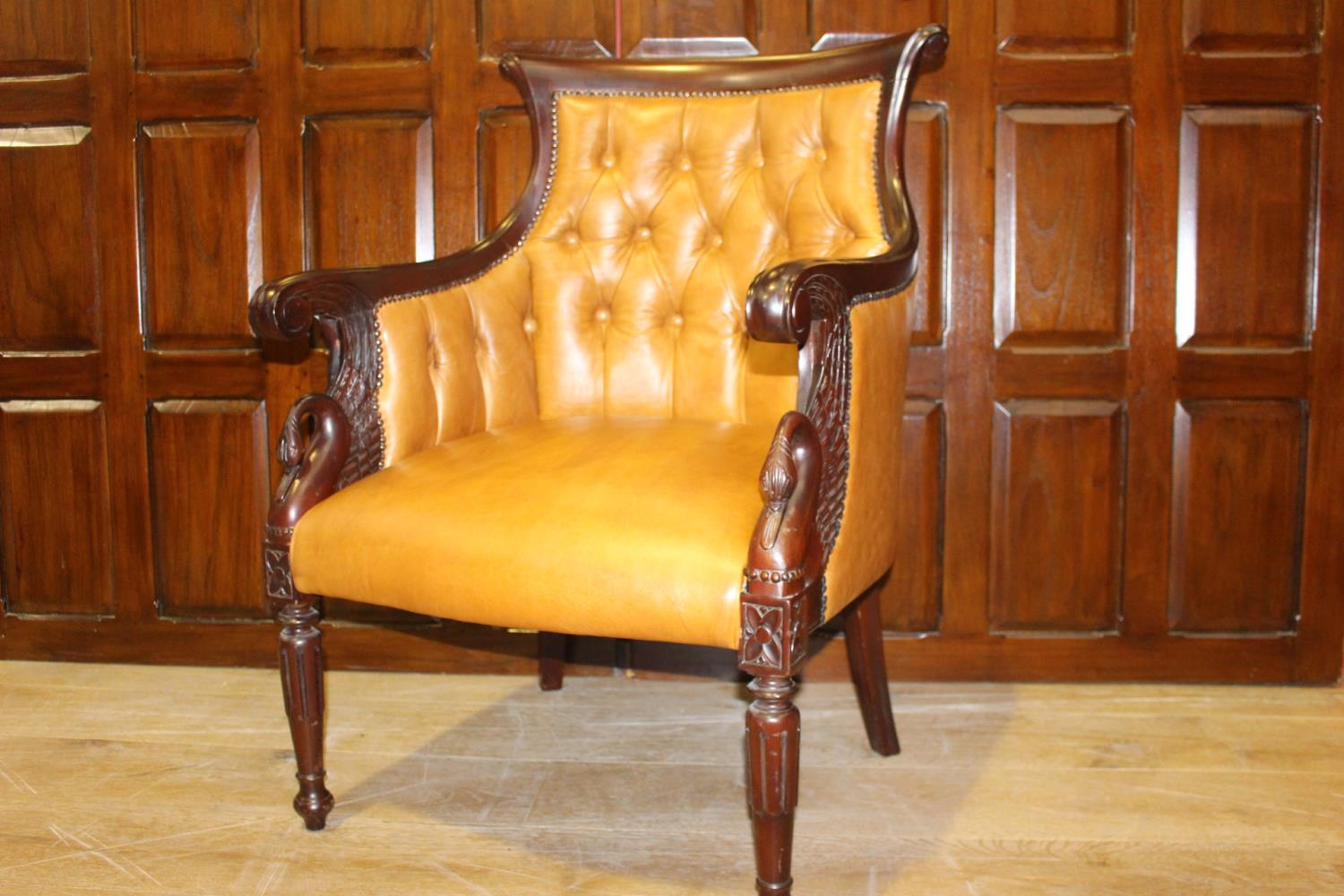 Carved mahogany and leather upholstered armchair