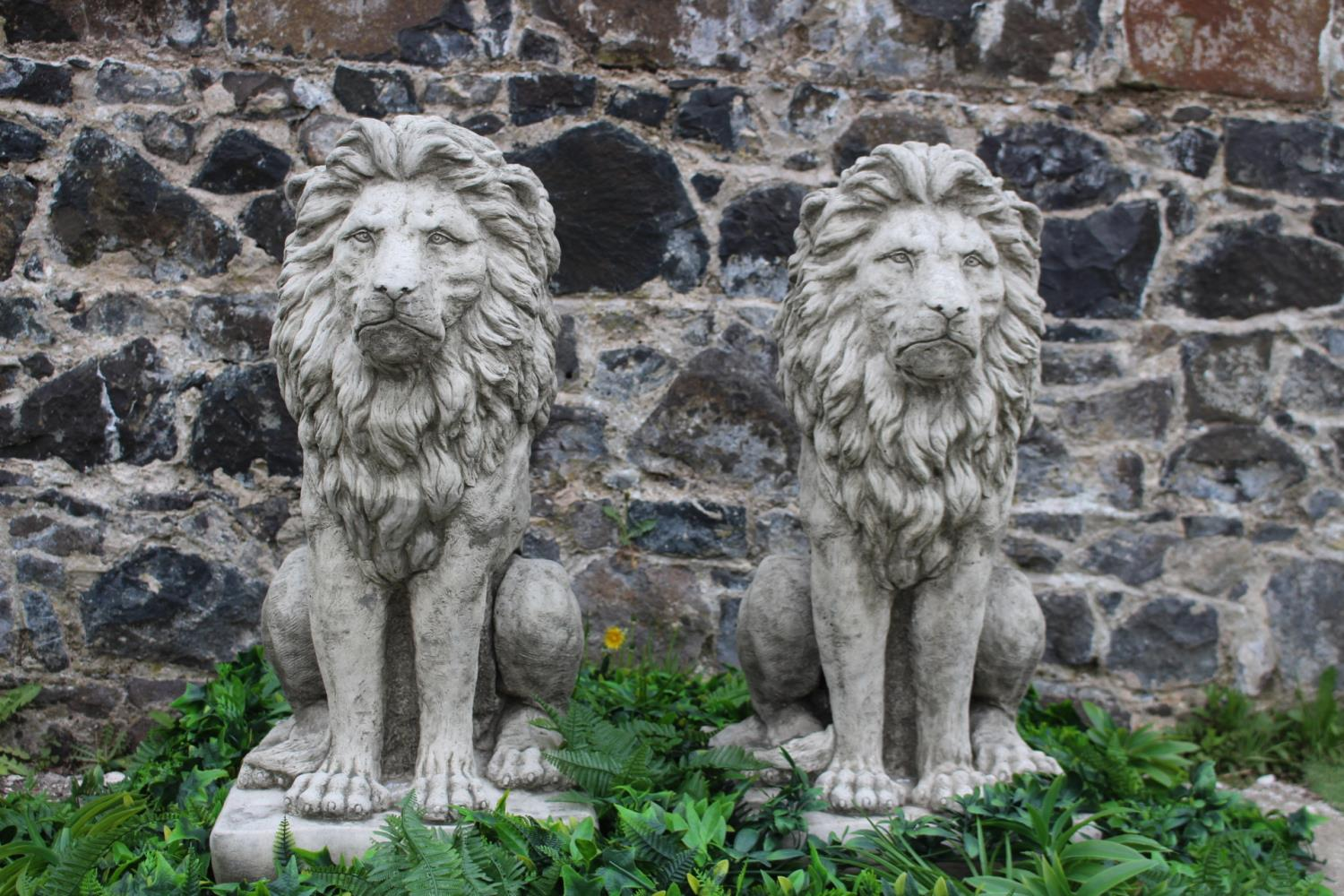 Pair of composition stone models of seated Lions