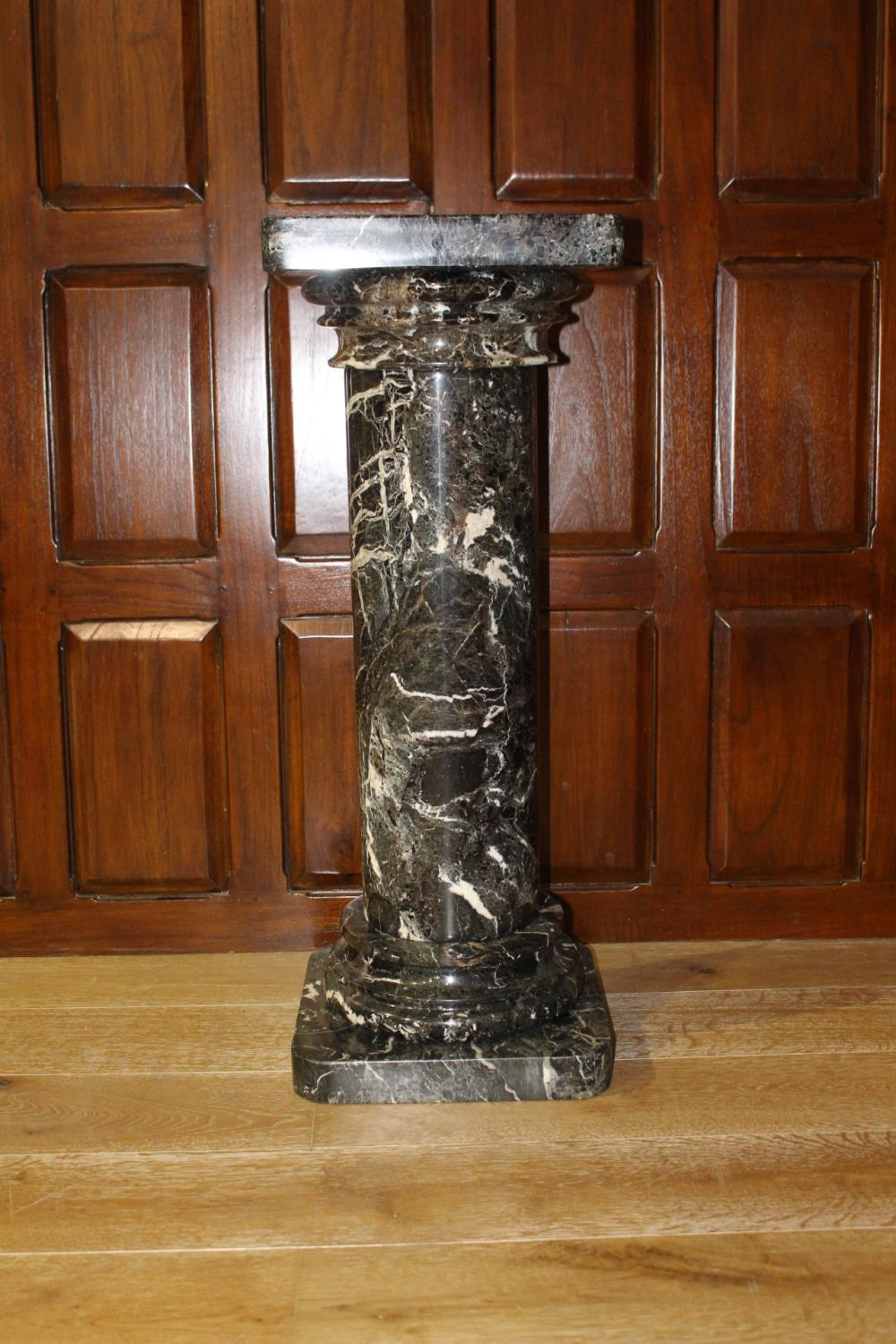 Marble pedestal with Corinthian top.