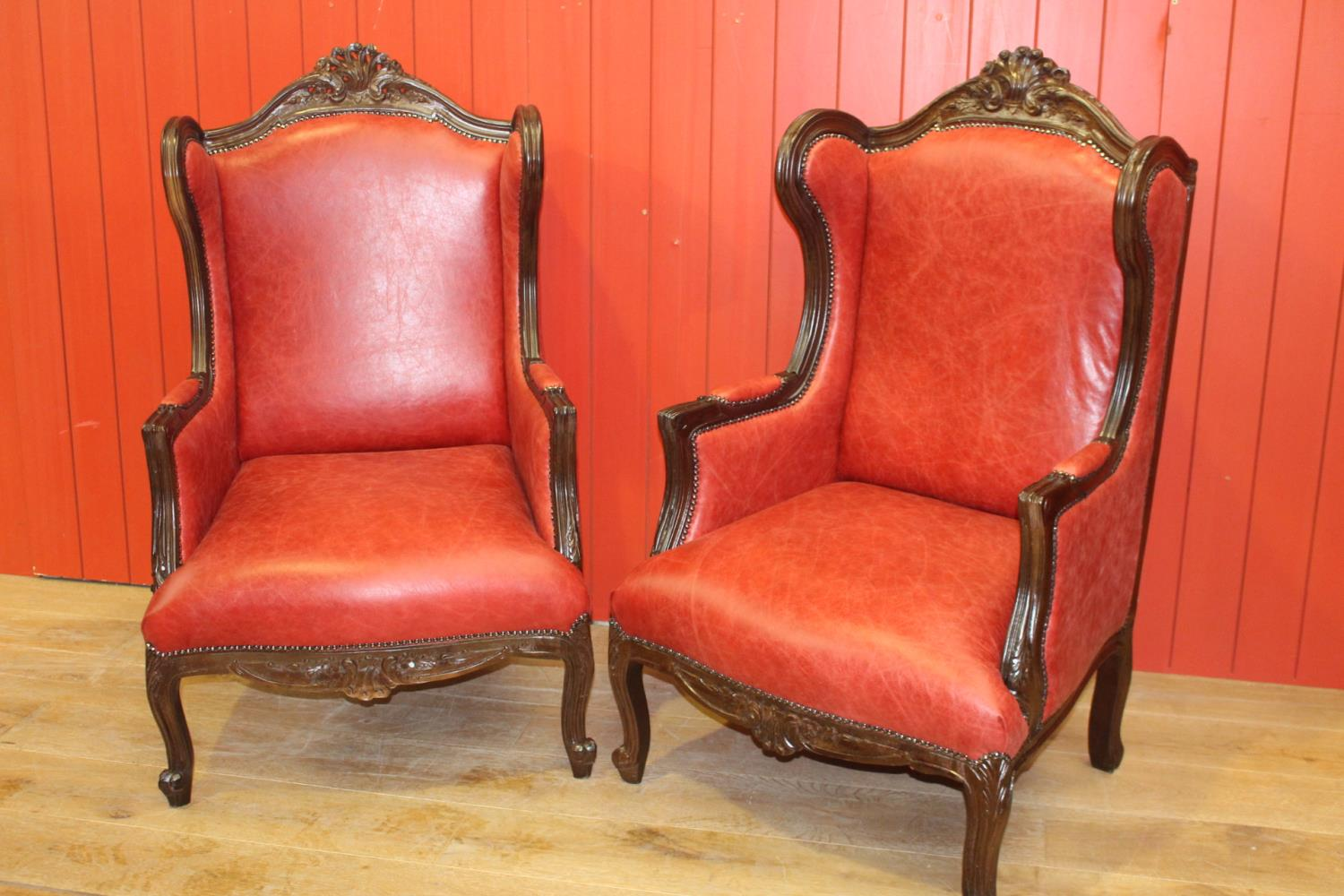 Pair of wing back leather upholstered armchairs