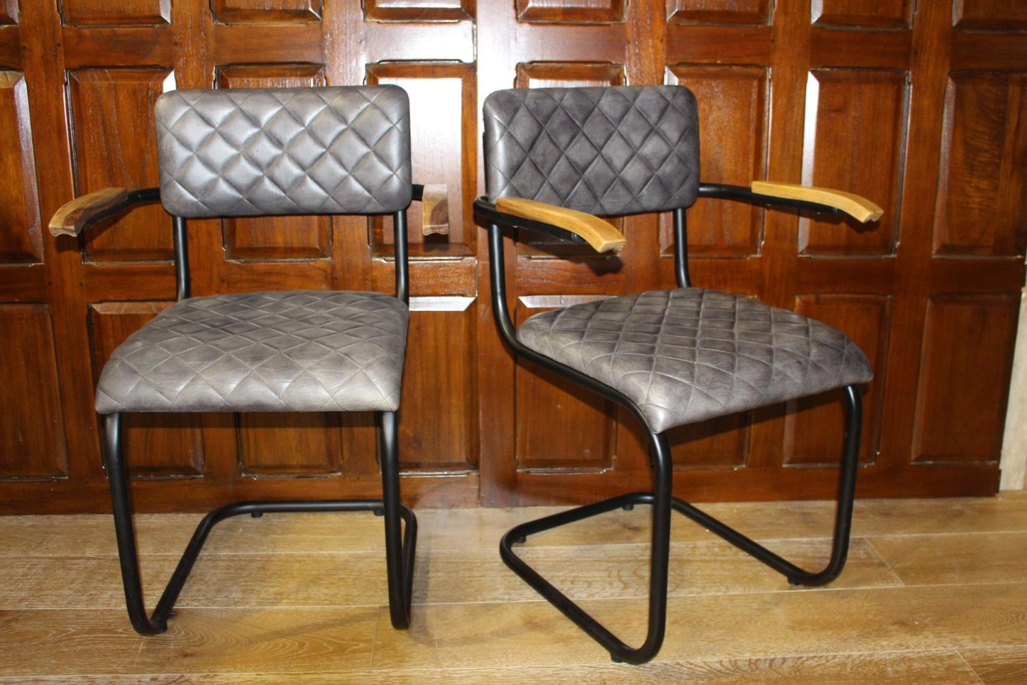 Pair of leather upholstered metal and wood armchairs.