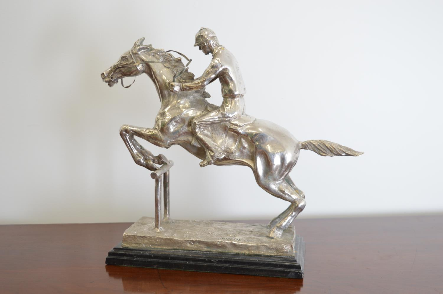 Silver plated model of a jumping horse and jockey