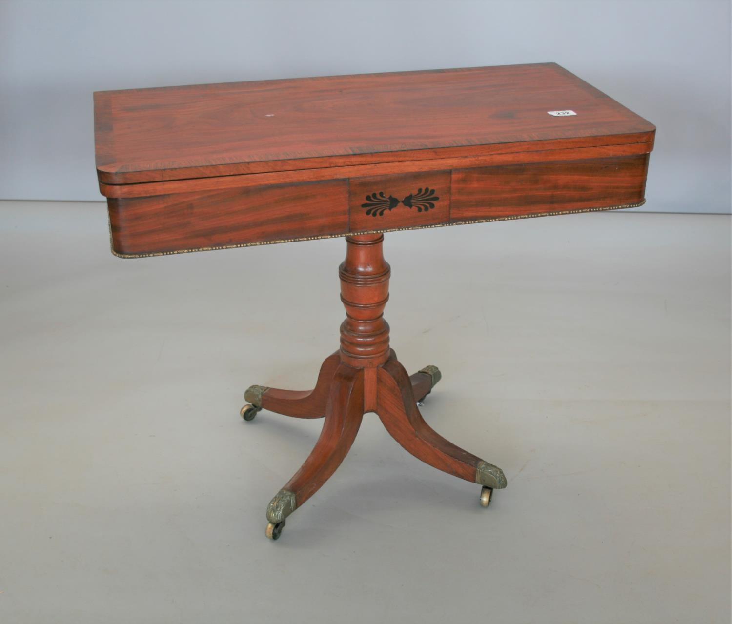 Fine Regency mahogany fold over tea table, the top with Rosewood cross banding and frieze with ebony