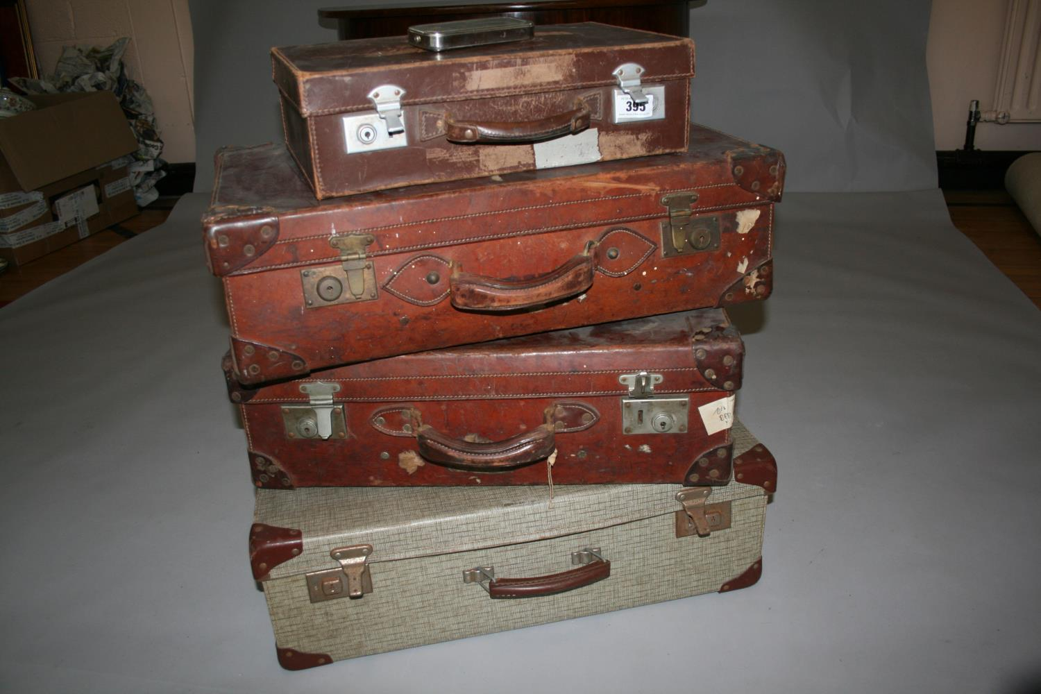 Four vintage leather suitcases, with compass, blade sharpener and wood plain.