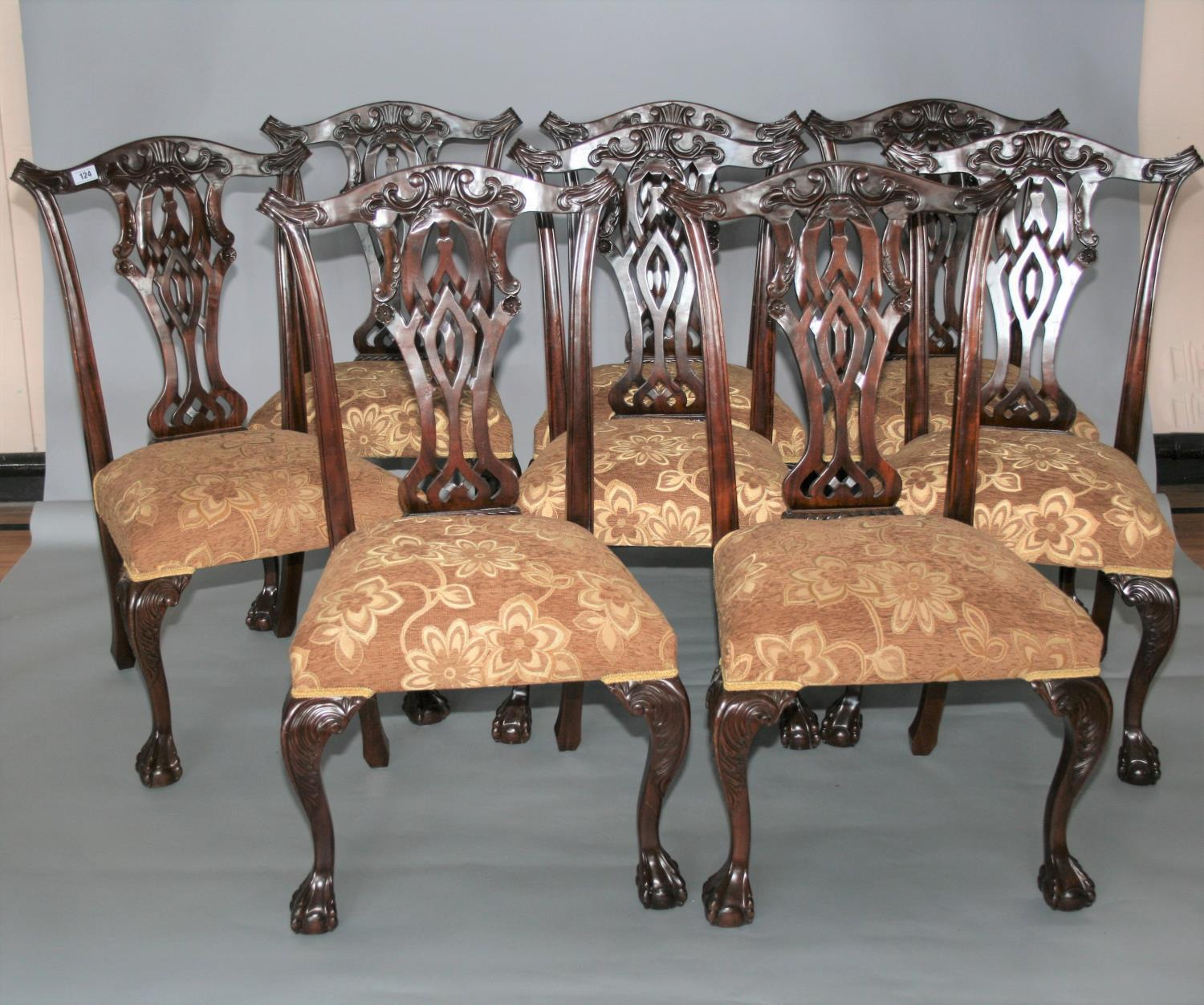 Set of eight Chippendale style dining chairs with floral gold upholstery. 59W x 103H