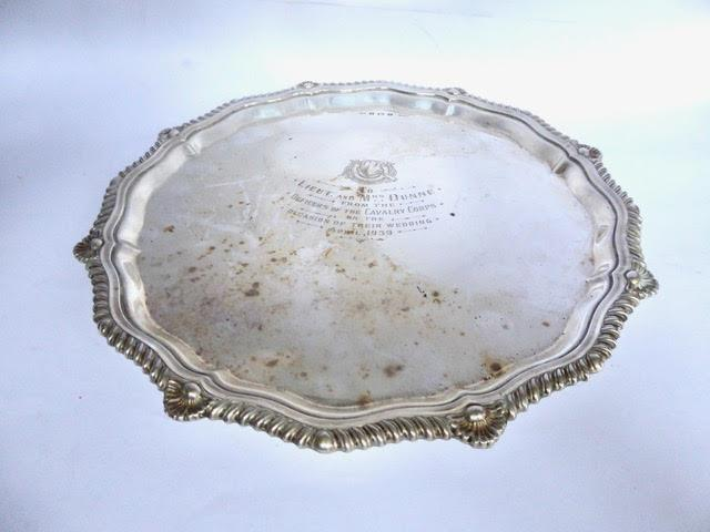 Silver salver of shaped circular form, with gadroon and shell border, On three bun feet with