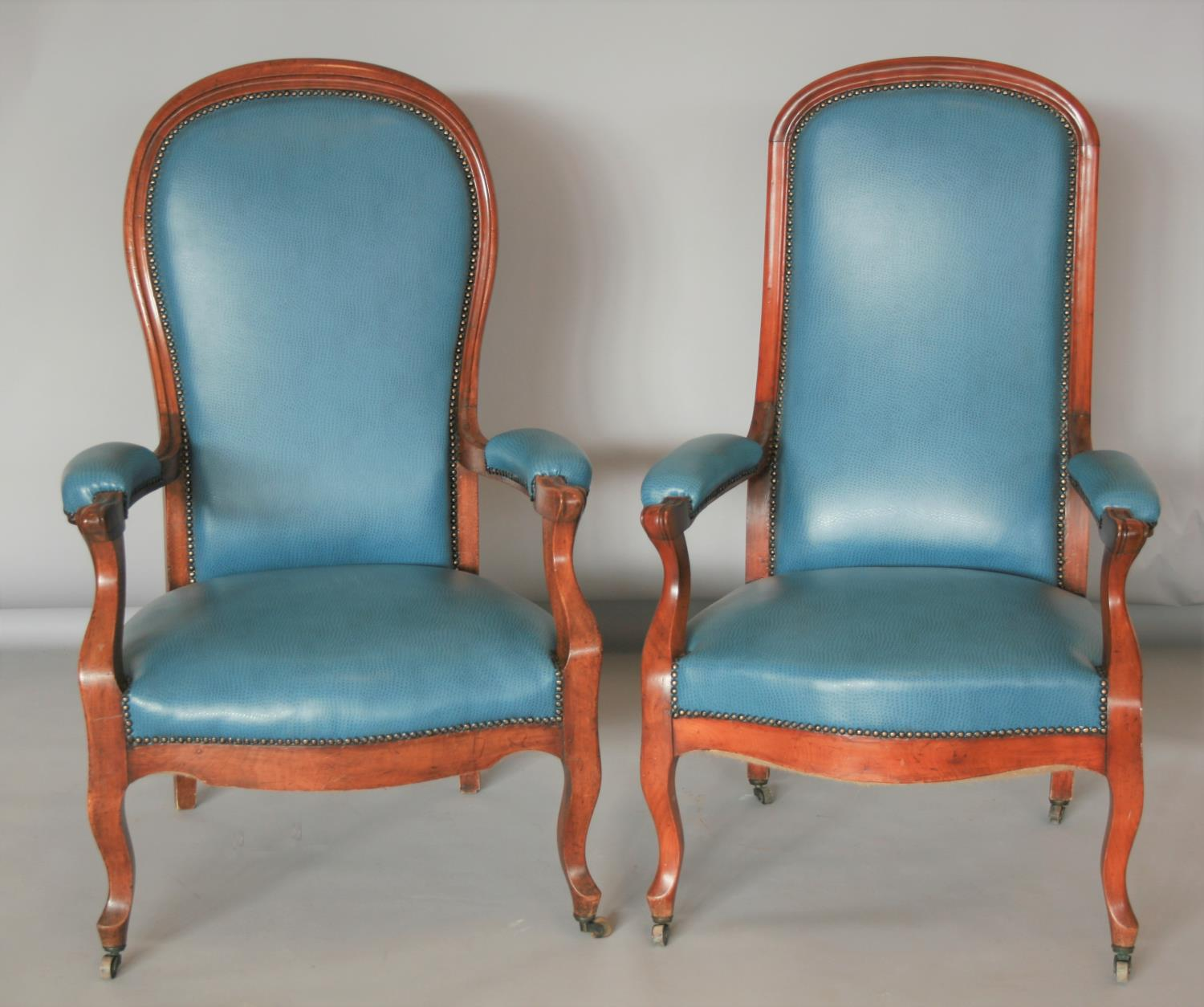 Near pair of Edwardian mahogany armchairs, with speckled hide upholstery.