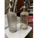 Two Thwaites advertising soda syphons.