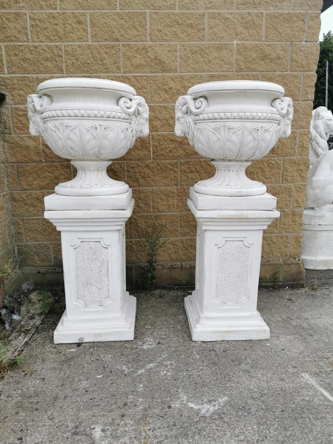 Pair of moulded stone Urns on pedestals.