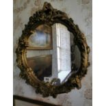 Moulded plaster gilt oval mirror.
