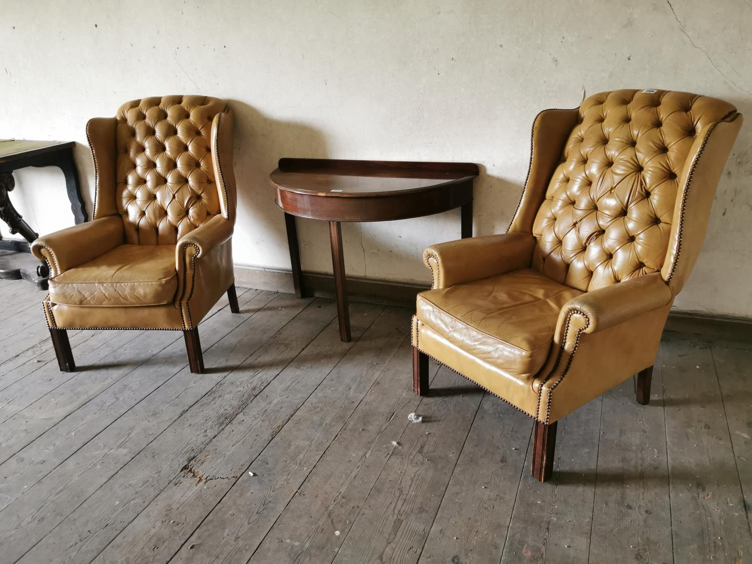 Pair of tanned leather arm chairs.