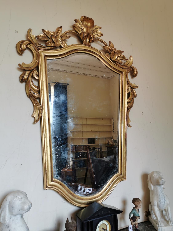 Gilt wall mirror surmounted with foliage