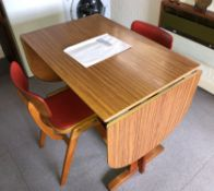 1970S FORMICA DROP FLAP KITCHEN TABLE AND TWO RED VINYL COVERED CHAIRS