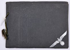 A small Third Reich photograph album, the cover mounted with an aluminium cap eagle, containing 12
