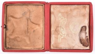 A red cloth covered case for a Turkish Gallipoli Star, the lid impressed with toughra mark, the