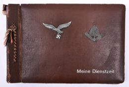 A Third Reich photograph album, the cover mounted with Luftwaffe metal cap eagle and RAD metal cap