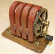 A hand-cranked magneto machine of brass and copper construction with 4 permanent magnets. 'No.8'
