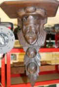 A mahogany bracket for a clock etc. The support decoratively carved with a head of a king surrounded