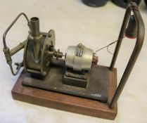 A Stuart Models dynamo. Rated at 4v. 1a. and 8000rpm. Connected to a brass steam driven fan and