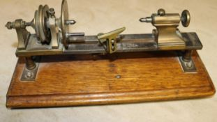 A small brass model of a basic wood turning lathe. Mounted on a hardwood plinth. Intended to be a