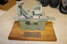 A small metal model of an industrial grinding machine. A well detailed model presented as a
