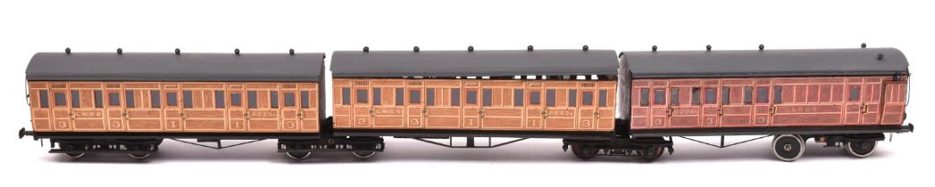 An O gauge possibly Leeds Model Co. LNER 3-car articulated coach set. Teak coaches mounted on 4