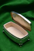 A silver trinket box on raised feet with blue guilloché enamel panel in lid and padded interior.