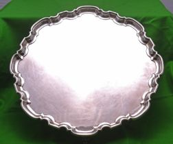 A substantial silver tray on four scrolled feet with decorative raised edge. Hallmarked for