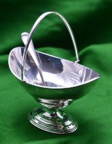 A silver sugar bowl and pierced spoon. A plain oval bowl with hinged handle. Hallmarked London 1904,