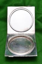 A silver powder compact with engine turned case, blue guilloché enamel lid and fitted mirror inside.