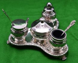 A decorative silver 4-piece condiment set. On a triangular stand raised on 3 feet with blue glass