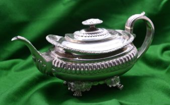 A Georgian rounded rectangular silver teapot with gadrooning decoration to the body, leaf-embossed